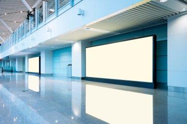 Airport passengers and blank billboard