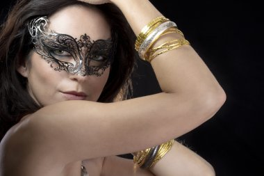 Sexy woman with venetian mask and gold and silver bracelets