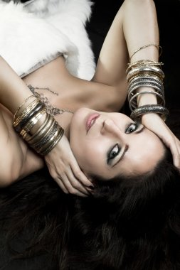 Woman lying and sensual with bracelets of gold and silver, green