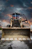 Fotografie Bulldozer, gelber Traktor auf dramatischem Himmelshintergrund