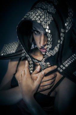 Beautiful brunette woman in armor formed by mirror