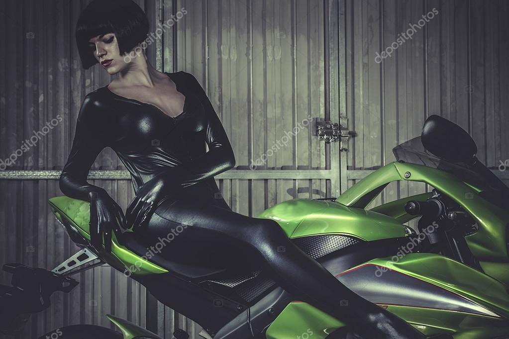 Woman in  latex mounted on a motorcycle