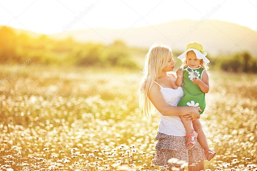 Mother and little daughter in a camomile field