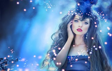 Young beautiful lady in blue dress in fairy forest