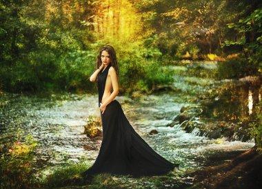 Beautiful girl in black dress in fairy forest