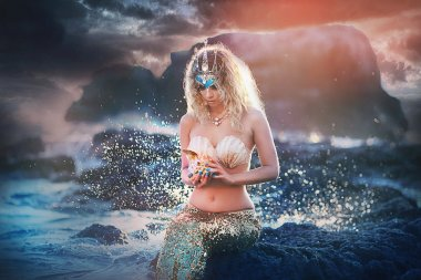 Beautiful fashionable mermaid sitting on a rock