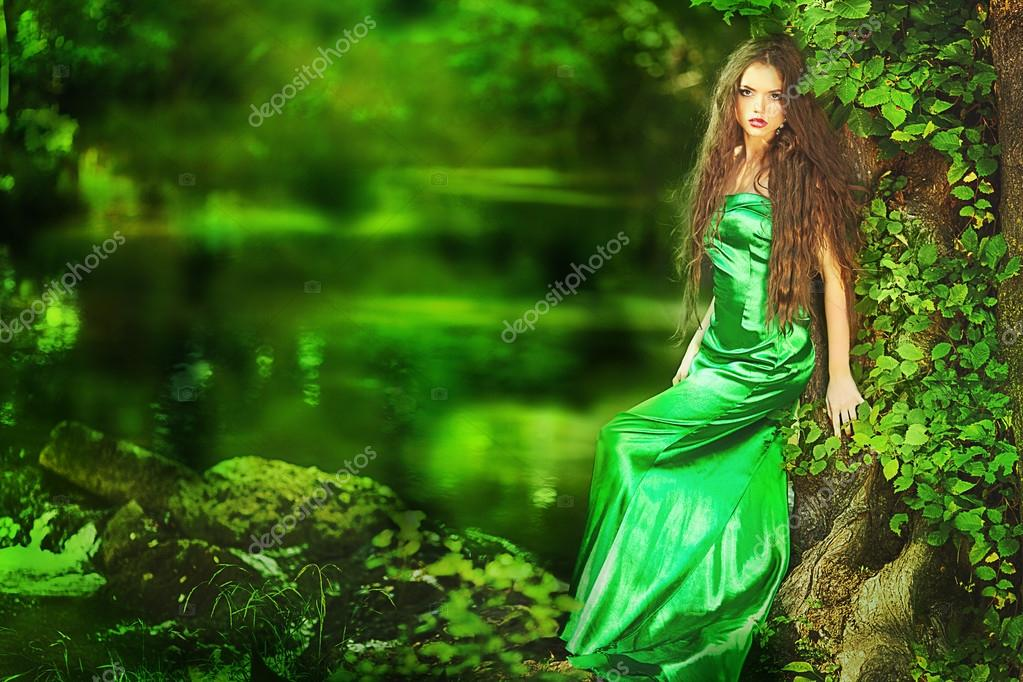 Beautiful girl in green dress in fairy forest