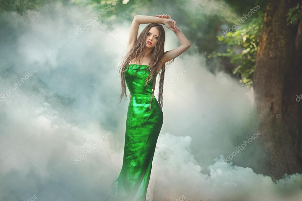 Beautiful girl in green dress standing in fog in the forest