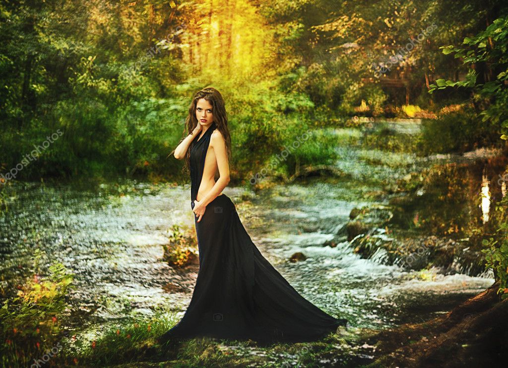 Beautiful girl in black dress in fairy forest