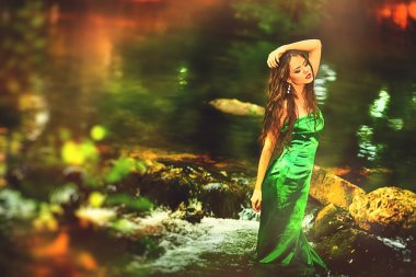 Beautiful girl in green dress in the forest pond