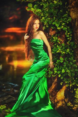 Beautiful girl in green dress in fairy forest
