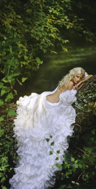 Blonde bride angel in long white skirt standing in forest