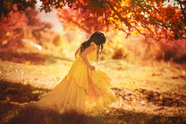 Beautiful girl in a yellow dress walking the air in the forest