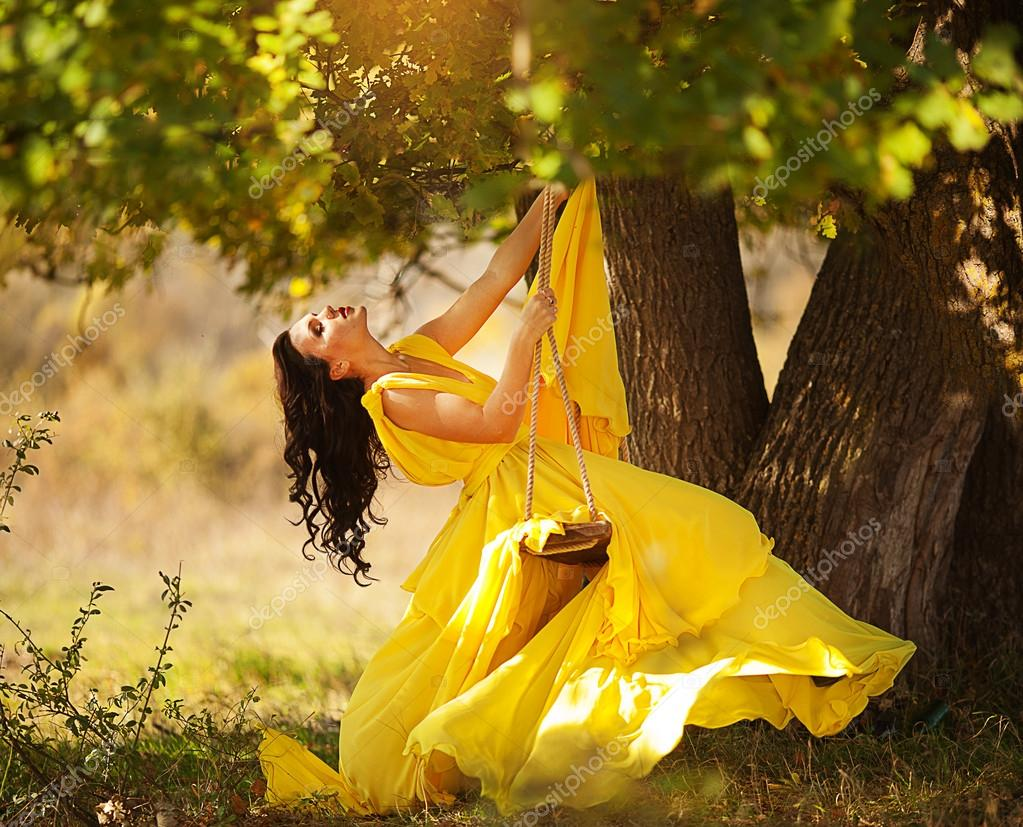 Beautiful girl in a yellow dress riding on a swing