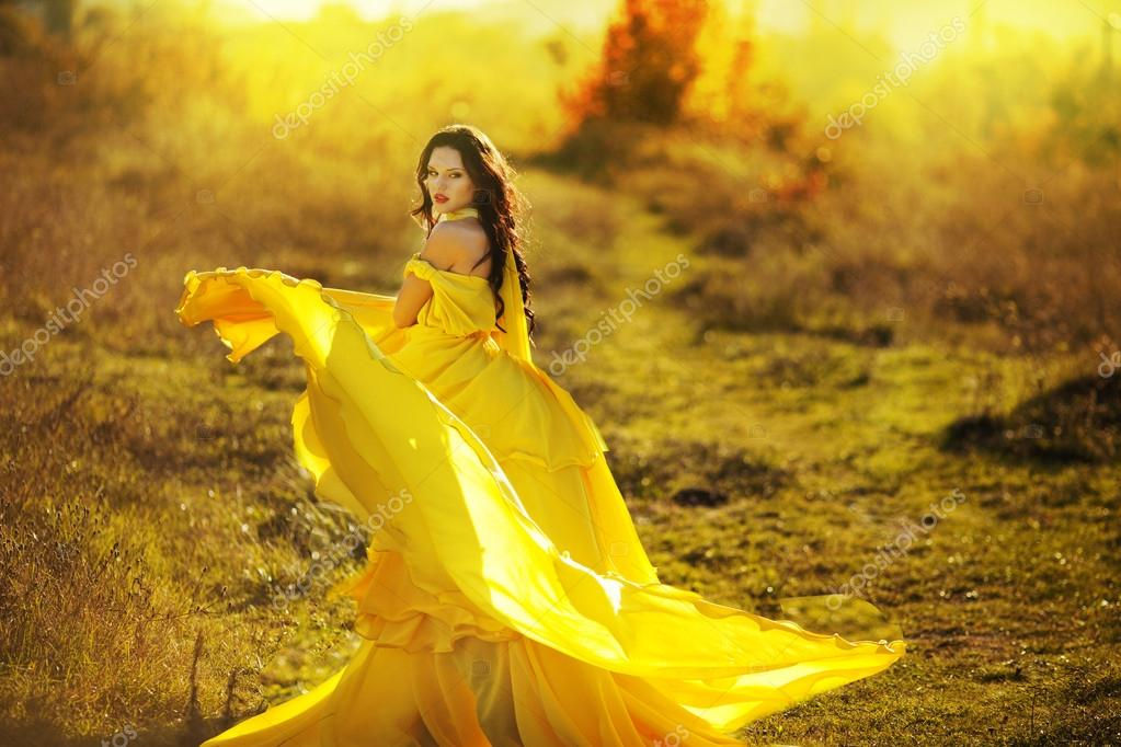 Beautiful girl in a yellow dress air