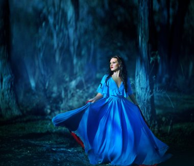 Beautiful girl in blue dress walking in the magical forest