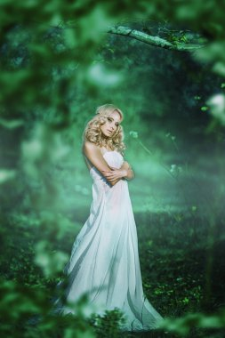 Young beautiful lady in white dress in fairy forest