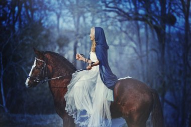 Beautiful blonde girl in white dress on a horse