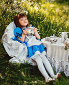 Photo Beautiful little girl in a blue dress with ceramic teapot