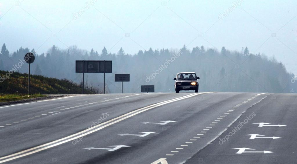 Highway with cars in the country in the autumn