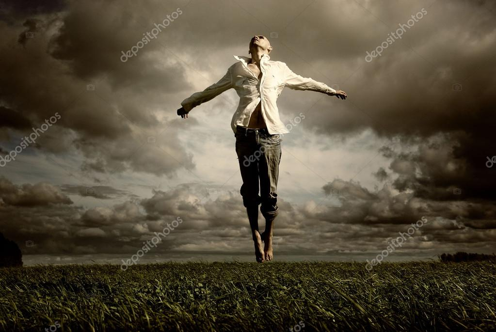 Man flying over a green meadow