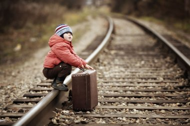 Boy sitting in a suitcase near the railway journey