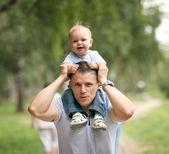 Apa a parkban játszó kisfiú