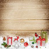 Fotografie Weihnachtsschmuck und Geschenke im Schnee auf einem hölzernen Hintergrund