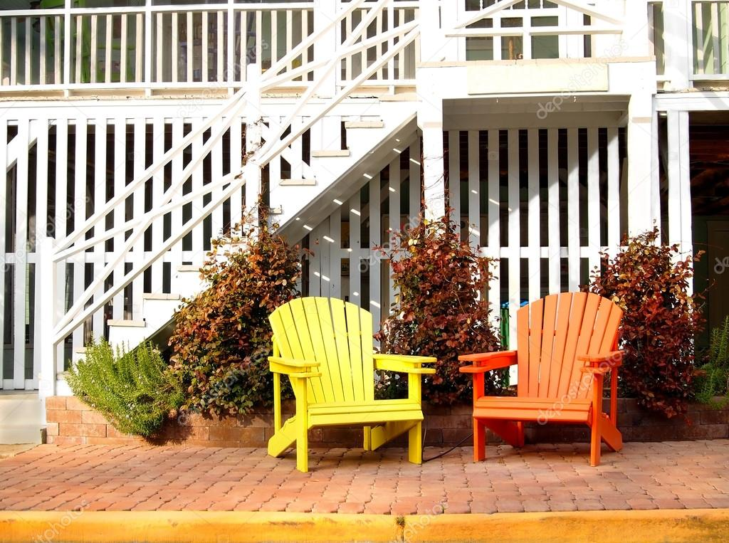 A Pair Of Wooden Adirondack Chairs, One Yellow And One Orange, In Front Of  A White Beach House. U2014 Photo By Duckeesue