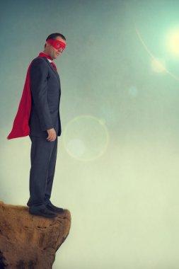 superhero businessman on a precipice