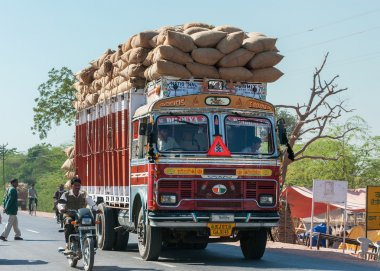 Nagaur in Rajasthan India - February 2011 - Overloaded dump truck filled with jute bags on the road.