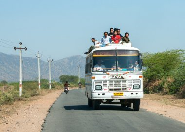 Rajasthan in India - February 2011 - Public transport bus with plenty of passengers on the roof driving on the road.