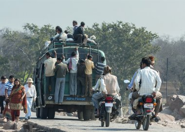 India Orchha - 21 February 2011 - Overloaded public transport bus carrying people on top and hanging out at the back.