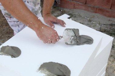Trowel spreading mortar on styrofoam insulation of wall stock vector