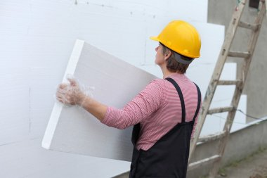 Female worker carry styrofoam sheet insulation at construction site stock vector
