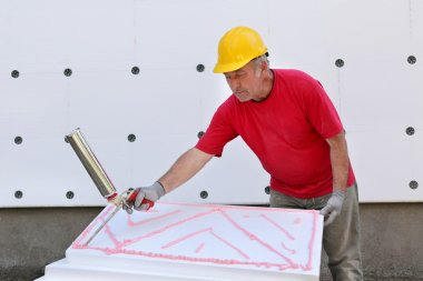 Worker applying polyurethane expanding foam glue with gun applicator stock vector