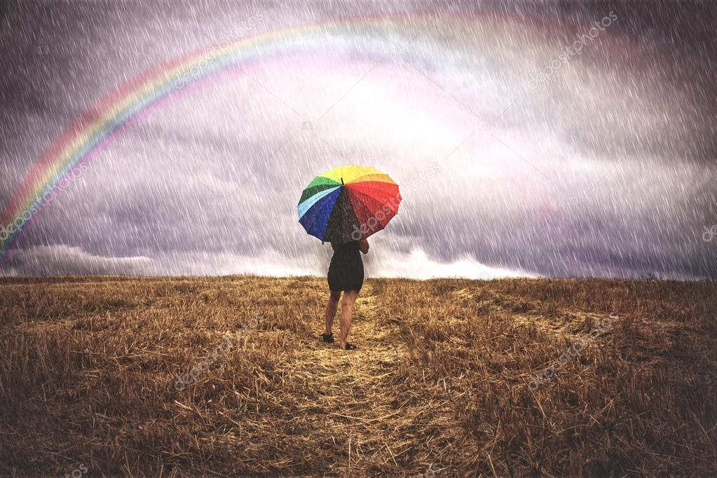 Woman in field with colorful umbrella in the rain