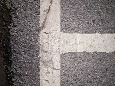 Dirty view of asphalt with distinct white stripe