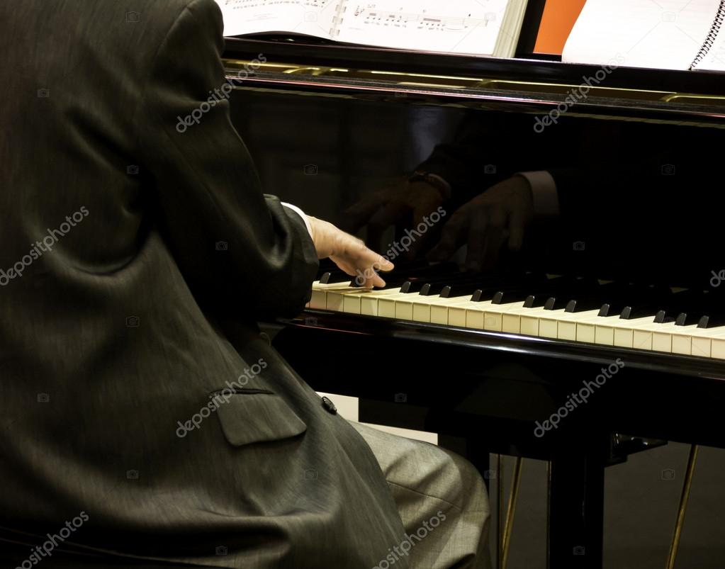 Male hands playing piano.