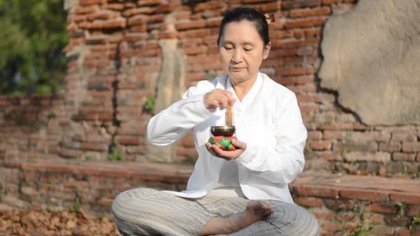 Žena hrající tibetské mísy, tradičně se používá k pomoci meditace v buddhistické kultury