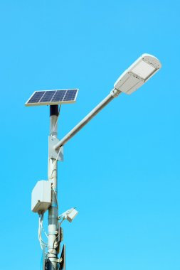 Solar panel powered street lamp on blue sky background