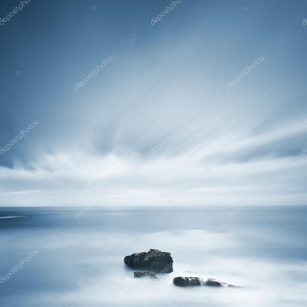 Dark rocks in a blue ocean under cloudy sky in a bad weather.