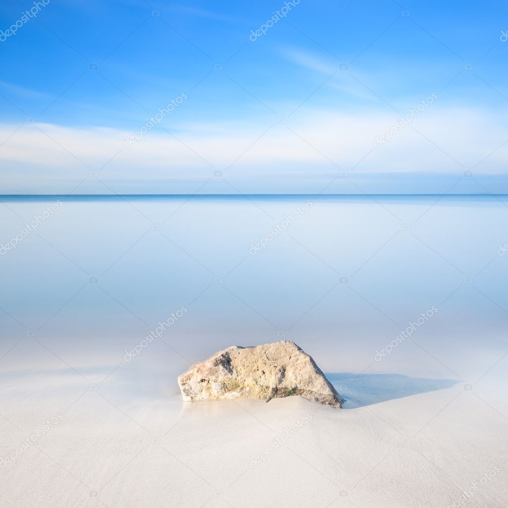 Rock on a white sand beach and sea on horizon.