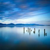 Dřevěné molo nebo mola zůstává na modré jezero a západu slunce a obloha reflexe na vodě. Versilia Toskánsko, Itálie
