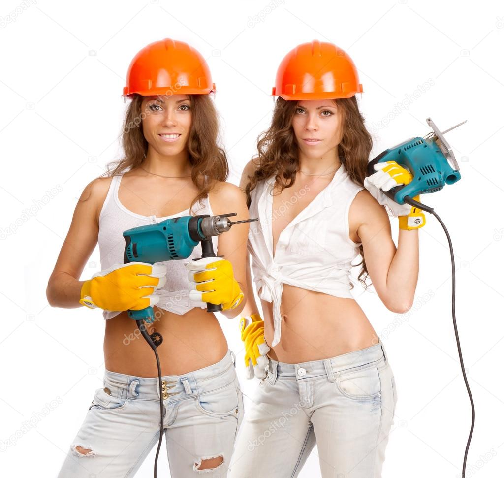 Gemini girls in orange helmets with an electric drill and electric saw on a white background.