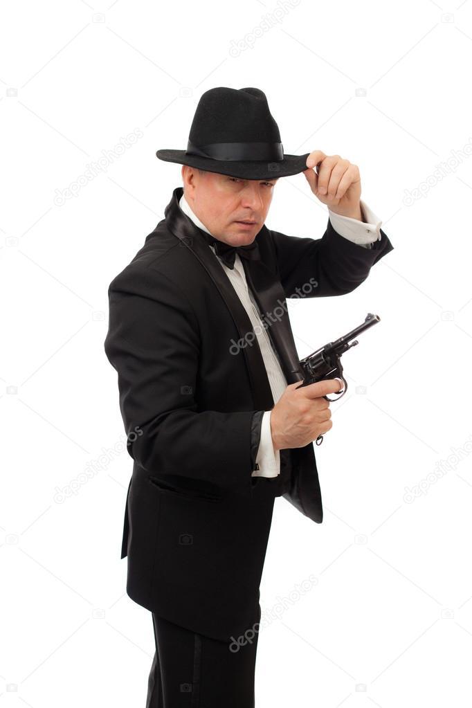 L uomo elegante in smoking con un cappello e un revolver su sfondo bianco–  immagine stock 5f9b3bd1eba8