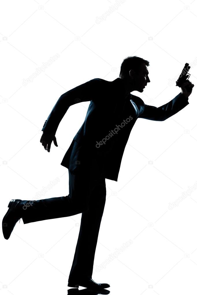 comprimento total de homem de silhueta correndo segurando a arma
