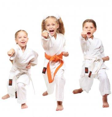 Three girls dressed in white kimono perform punch
