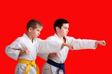 Confident athletes are training blows arms on the red background