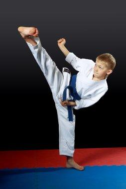 In white karategi athlete doing kick yoko-geri right foot